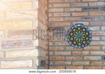dart arrow missing the center of target. dartboard on brick wall with sunrise. business and marketing concept.