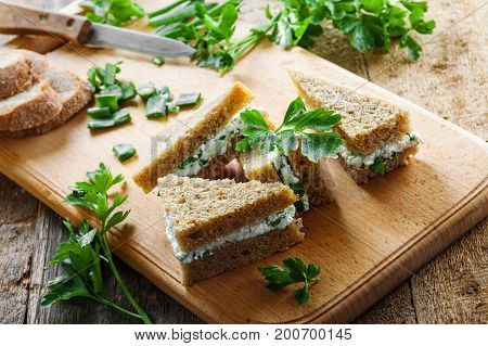 Cream cheese sandwiches with fresh parsley and green onion on a rustic table. Healthy homemade appetizer. Close-up shot.