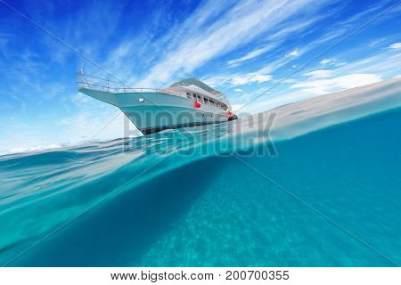 Small safari boat. Beautiful split shot under and above water. Travel lifestyle, water sport outdoor activities, swimming and snorkeling