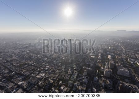 Smoggy afternoon aerial view of urban downtown buildings, streets and towers in Los Angeles, California.