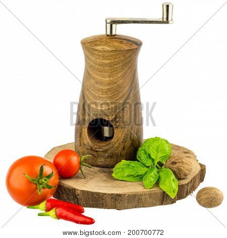 Muscat mill on wooden board with basil leaves, tomato, chili and nutmeg