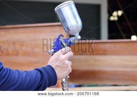 Hands of worker holding spray paint gun in home workshop.