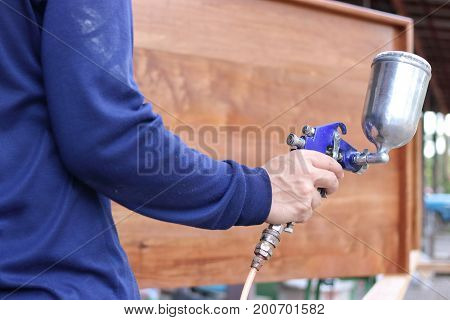 Hands of industrial worker holding spray paint gun in the workshop background.