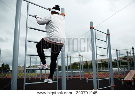Young woman in sportswear ascending on sports facilities on stadium