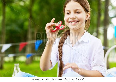Pretty youngster playing with fidget spinner outdoors