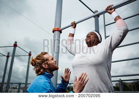 Determined oversized female hanging on facilities bars while trainer encouraging her