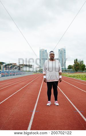 Young plump woman in activewear standing on one of racetracks