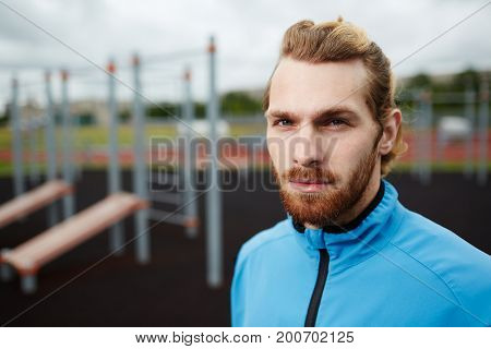 Young sports trainer in activewear on sport ground with facilities