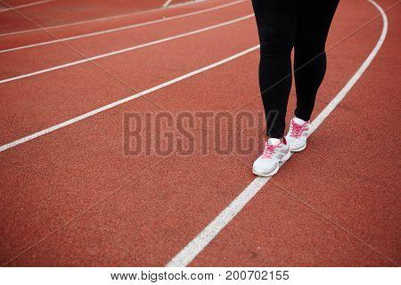 Legs of plus-sized woman walking down white line on stadium