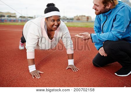 Young trainer encouraging oversized female during workout on stadium