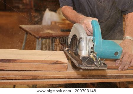 Selective focus on hands of senior carpenter cutting a piece of wood with electric circular saw in carpentry workshop