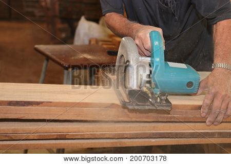 Electric circular saw is being cut a wood board by workers in woodwork shop.