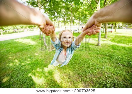 Little child being whirled by her parent over green grass in park