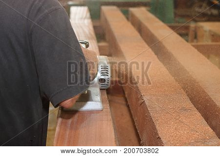 Back view of hands of carpenter using electric planer with wooden plank in carpentry workshop with copy space background. Selective focus and shallow depth of field.