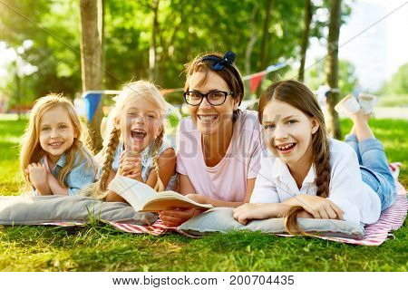 Restful and joyful kids and their teacher spending leisure with book of tales in park