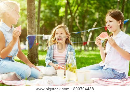 Restful kids eating water-melon at picnic on green lawn on weekend