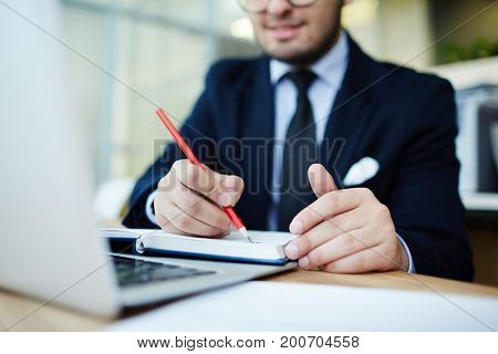 Businessman making notes in notebook in front of laptop