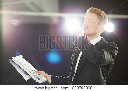 Handsome red-haired speaker rehearsing speech for effective business presentation while standing at dark conference hall, waist-up portrait shot