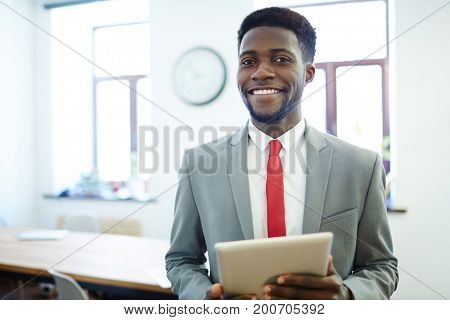 Successful employer with tablet looking at camera