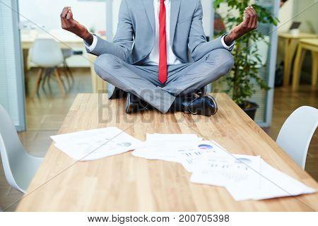 Manager in formalwear meditating on desk in office