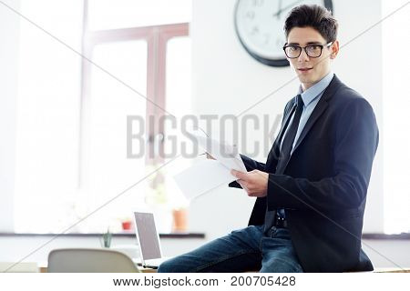 Young economist with papers working in office