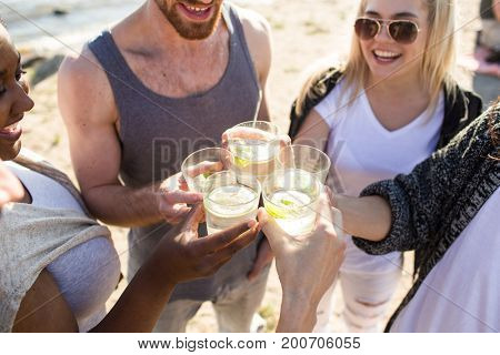 Joyful friends toasting with glasses of caipirinha at beach party