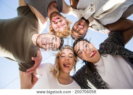 Humorous friends grimacing and showing tongues while huddling