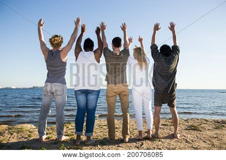 Rear view of ecstatic teens standing on sandy beach in front of water