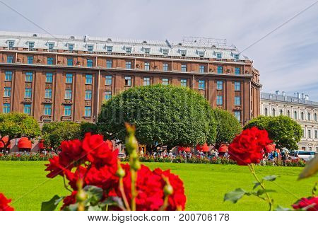ST PETERSBURG RUSSIA - AUGUST 15 2017. Famous Astoria hotel at Bolshaya Morskaya street in St Petersburg Russia in sunny day with red flowers on the foreground. St Petersburg Russia landmark in cloudy day