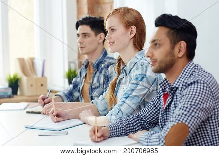 Attentive students making notes during lecture or conference