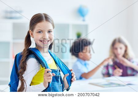 Pretty youngster with rucksack on background of two schoolboys