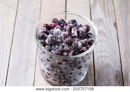 Frozen black currant on a wooden background