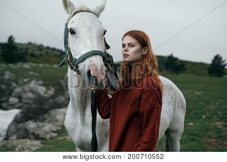 Beautiful young woman walking in the mountains with her horse.