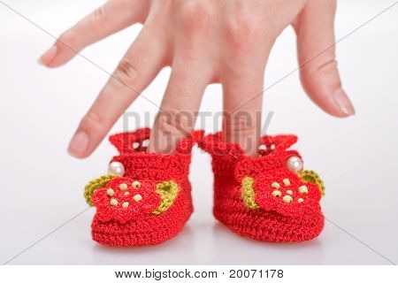 Crocheted Booties For A Girl In The Woman Hand