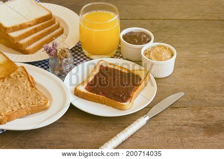 Toast bread with homemade strawberry jam and peanut butter served with orange juice. Homemade toast bread with jam and peanut butter on wood table for breakfast. Delicious toast bread ready to served.Toast bread with spread ready to served.