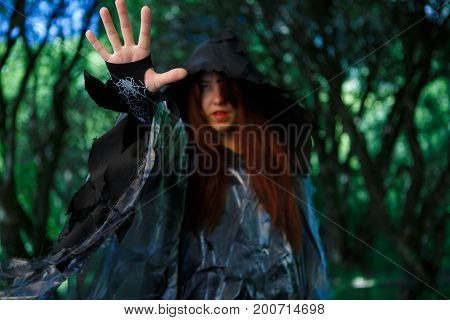 Image of witch in black cloak with outstretched hand in forest