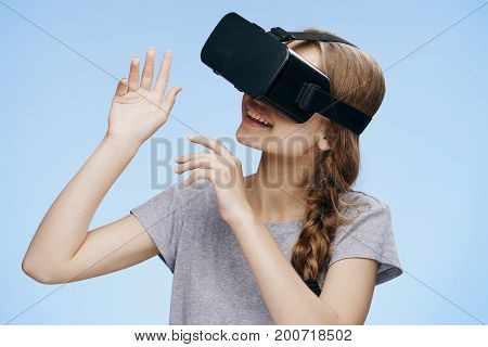 Beautiful young woman on a blue background with virtual reality glasses.