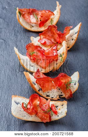 Appetizer bruschetta with jerky prosciutto on thinly sliced ciabatta bread on stone slate background close up. Delicious snacks sandwiches crostini antipasti. Top view