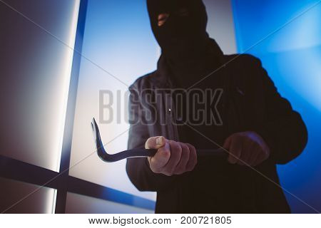 Burglar Using A Crowbar To Break Into A House
