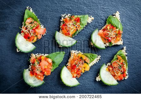 Appetizer canape with chopped vegetables and sesame on stone slate background close up. Delicious snacks sandwiches crostini bruschetta antipasti on party or picnic time. Top view