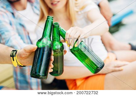 Wonderful day! Cheers! Group of young people holding and toasting with green bottles of beer on river background. Celebrating oktoberfest with friends outdoor. Barbecue hanging out, relaxing concepts.