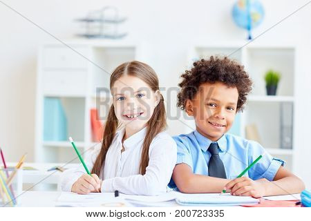 Multi-racial schoolchildren with pencils sitting by desk close to one another