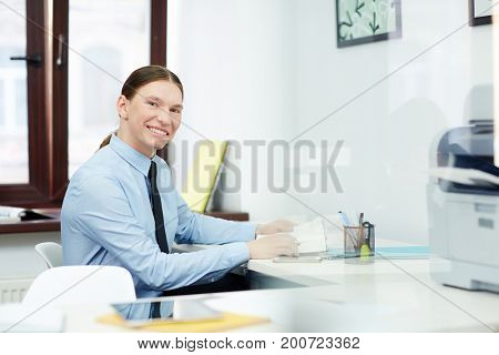 Smiling young white collar worker with ponytail posing for photography while sitting at desk and taking notes, interior of modern office on background