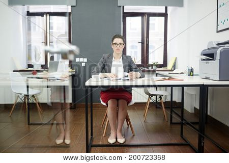 Full length portrait of confident white collar worker looking at camera while writing down business ideas in notepad, interior of spacious open plan office on background