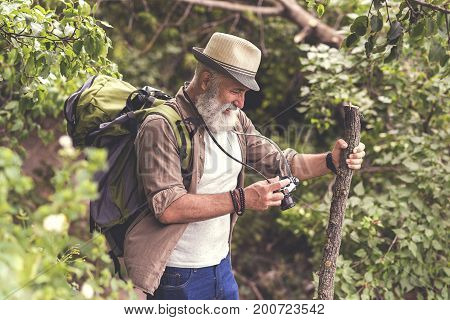 Joyful senior man is reviewing photos on his camera screen. He is standing in forest with backpack and smiling