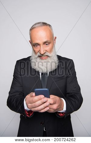 Infuriated Senior Man Looking At Smartphone