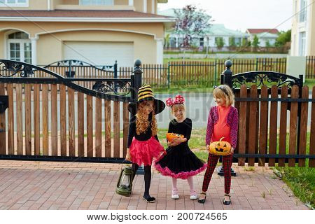 Trick-or-treat girls standing by fence of house they visited