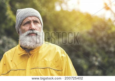 Portrait of serious old bearded man traveling in wild nature by alone. He is looking forward pensively. Copy space in right side