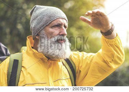Thinking about nature. Portrait of pensive mature man looking forward with seriousness. His hand covers his eyes from sunshine. Traveler is standing and carrying rucksack