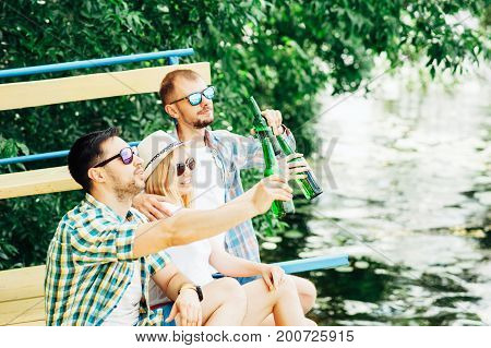 Group of young people sitting on the beach toasting and drinking beer from bottles. Friendship, barbecue, oktoberfest, relaxing concepts. Good time with friends outdoor. Men and woman hanging out.